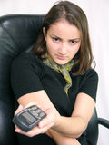 Bad news. Angry girl with a mobile phone in her left hand. Sitting in an executive chair royalty free stock photography