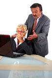 Bad News. A senior businesswoman in her fifties is working on a laptop in an office and seems to be shocked. Her boss behind her is angry. Isolated over white Royalty Free Stock Images