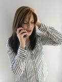 Bad News. A woman getting really bad news on the phone Stock Image
