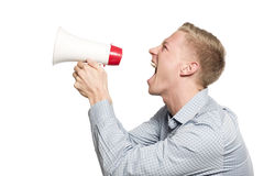 Furious businessman shouting with megaphone. Bad news: Angry businessman shouting with megaphone isolated on white background Royalty Free Stock Photos