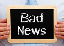 Bad News - Businessman holding chalkboard with text. In his hands royalty free stock images