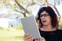 Bad news. Closeup portrait, upset young woman with curly black hair, astonished surprised,  large eyes in black glasses by what she sees on her gray silver Stock Photo