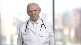Bad news from the doctor. Portrait of an old serious nervous stressed doctor getting ready to tell bad news to a patient. Bright abstract blurred windows stock video footage