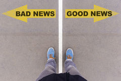 Bad news, good news text arrows on asphalt ground, feet and shoe Royalty Free Stock Photography