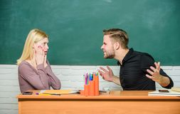 Bad news for her. Frustrated teacher and schoolmaster sitting at desk. Handsome man and cute woman back to school. University or college students. High school stock photography