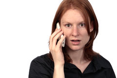 Bad News over Phone. A young woman talking on the phone and showing a stressed or shocked expression on her face. Isolated over white background Royalty Free Stock Images