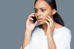 Bad news over the phone. Depressed young African woman talking on the mobile phone and touching face with hand while standing against grey background Royalty Free Stock Image