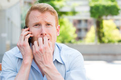 Bad news on phone. Closeup portrait, young man biting finger nails, worried about something he hears on phone, isolated outdoors background Stock Images