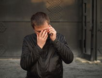 Bad news. Young adult man is devastated by bad news. Has he just lost someone ....? Dark industrial surroundings stock image