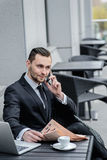 Bad news. Young handsome man talking on the phone in a suit. Royalty Free Stock Photography