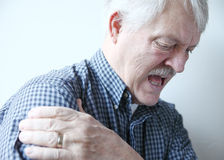 Bad pain in shoulder of senior man. Older man with pain in his shoulder royalty free stock photography