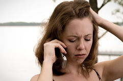Bad Phone Conversation. Young woman listens on phone with worried expression on face. Florida bay in background stock photo