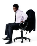 Bad posture back pain. Black businessman in pain from sitting on his office chair with bad posture, long working hours concept.  on white Royalty Free Stock Photo
