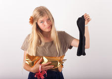 Bad present. Beautiful young woman not too impressed by her birthday or christmas present which is a pair of black stocks stock photos