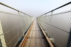 Bad prospects - suspension bridge in the fog. Small Bridge in the fog. Bad prospects for the future. Go your own way and allone stock photos