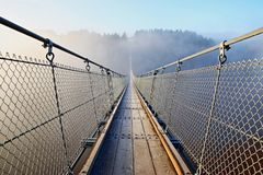 Bad prospects - suspension bridge in the fog. Small Bridge in the fog. Bad prospects for the future. Go your own way and allone royalty free stock photos