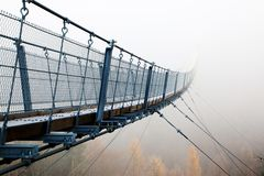 Bad prospects - suspension bridge in the fog. Small Bridge in the fog. Bad prospects for the future. Go your own way and allone stock image