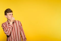 Bad rancid foul smell odour man coveing nose. Bad rancid foul smell. terrible odour. man holding his breath and covering nose. portrait of a guy on yellow stock photo