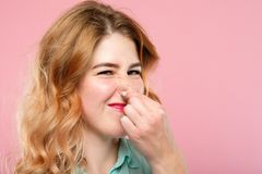 Bad rancid smell odor woman holding nose grimacing royalty free stock image