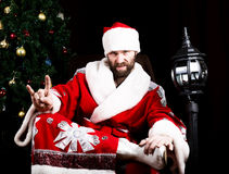 Bad rastoman Santa Claus doing different finger signs on the background of Christmas tree royalty free stock photography