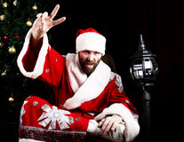 Bad rastoman Santa Claus doing different finger signs on the background of Christmas tree stock photos