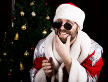 Bad rastoman Santa Claus holding the bag with gifts and scratching his beard on the background of Christmas tree. Bad brutal Santa Claus holding the bag with royalty free stock photography