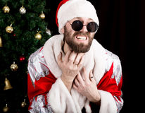 Free Bad Rastoman Santa Claus Holding The Bag With Gifts And Scratching His Beard On The Background Of Christmas Tree Stock Image - 81257341