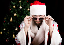 Bad rastoman Santa Claus holds round glasses and smiles, on the background of Christmas tree. different funy emotions.  royalty free stock photography