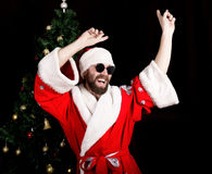 Bad rastoman Santa Claus smiles and fun dancing on the background of Christmas tree. Bad brutal Santa Claus smiles and showing middle finger sign on the stock photos