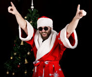Bad rastoman Santa Claus smiles and fun dancing on the background of Christmas tree. Bad brutal Santa Claus smiles and showing middle finger sign on the royalty free stock image