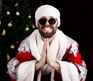 Bad rastoman Santa Claus smiles and making hands sign namaste on the background of Christmas tree Stock Photo