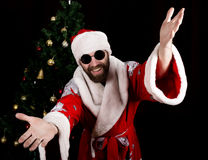 Bad rastoman Santa Claus smiles and spread his hands in different side on the background of Christmas tree. Bad brutal Santa Claus smiles and spread his hands in stock photo