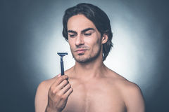 Really bad razor. Portrait of thoughtful young shirtless man looking at razor while standing against grey background Royalty Free Stock Image