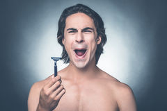 Bad razor. Young shirtless man holding razor and expressing negativity while standing against grey background Royalty Free Stock Photos