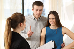 Bad real estate agent and discontent customers. Bad real estate agent attending to discontent customers in a house interior Royalty Free Stock Photos