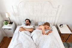 Bad relations in a relationship. Couple in bed. Couple bored with each other. Bad relations in a relationship royalty free stock images