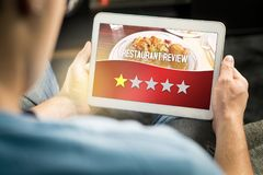 Bad restaurant review. Disappointed and dissatisfied customer. Bad restaurant review. Disappointed and dissatisfied customer giving terrible rating with tablet Stock Photos