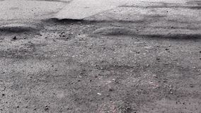 Bad road with holes in the asphalt stock footage