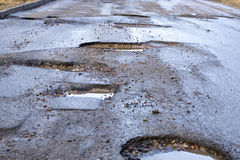 Bad road with pits in asphalt Royalty Free Stock Images