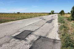 Bad road surface. Damaged road surface with patches - regional road in Negotin, Serbia Royalty Free Stock Image