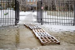Bad road to school, wooden pallets on a puddle stock photography
