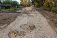 Bad road in the village,holes, hollows. The road to the village is very poorly repaired, the pits appear constantly Royalty Free Stock Image