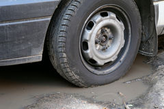 Bad road. Wheel and puddle. Royalty Free Stock Image