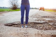 The bad roads. Bad roads - a girl stands in a hole in the road stock image