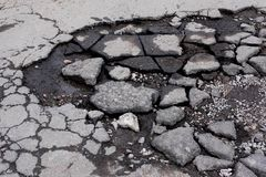 Broken pit with pieces of asphalt. Bad asphalt road. Destruction of roads, pits on the road royalty free stock photography