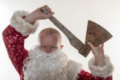 Bad Santa Claus with an ax. The concept of fun and unexpected advertising.  Royalty Free Stock Photos