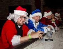 Bad Santa Claus. Several men in Santa Claus costume suits drinking at a bar Stock Image