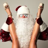 Bad santa claus in snow flakes sunglasses honding young sexy naked legs woman Stock Photos