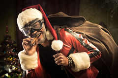 Bad Santa is coming. Bad Santa with goggles and cigar carrying a sack with gifts Royalty Free Stock Photos