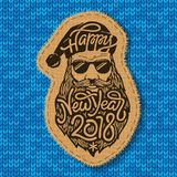 Bad Santa with glasses and big beard with the lettering Happy New Year 2018 on blue knitted background. Stitched. Bad Santa with glasses and big beard with the Stock Photography